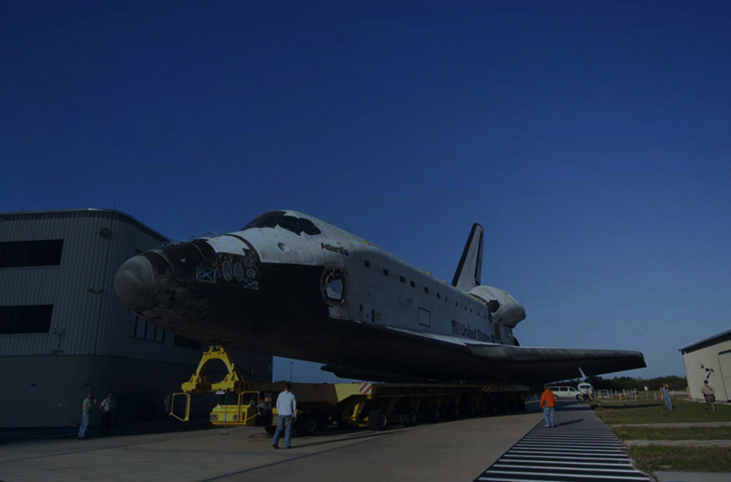 The Atlantis Space Shuttle being moved on some many wheeled customized vehicle.