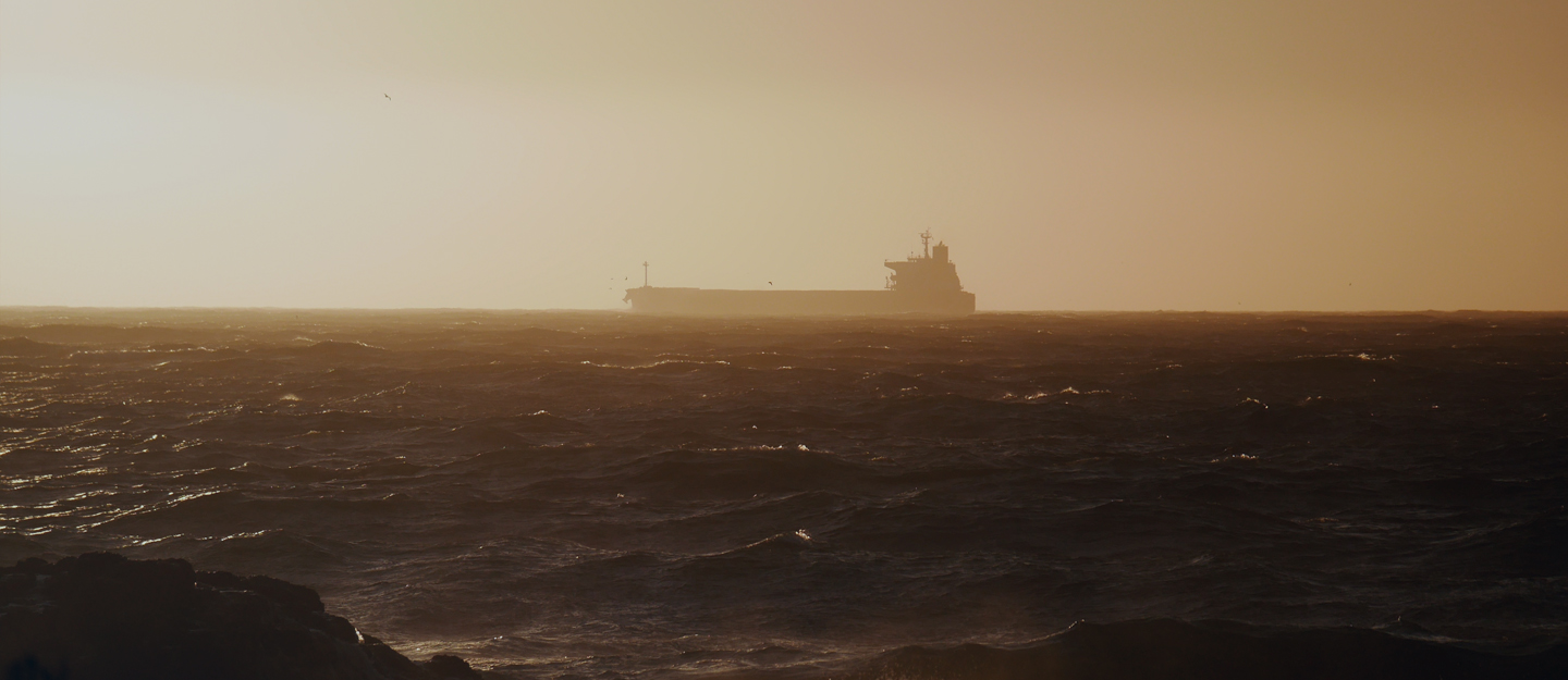 Rough seas with a hazy outline of a freighter ship.