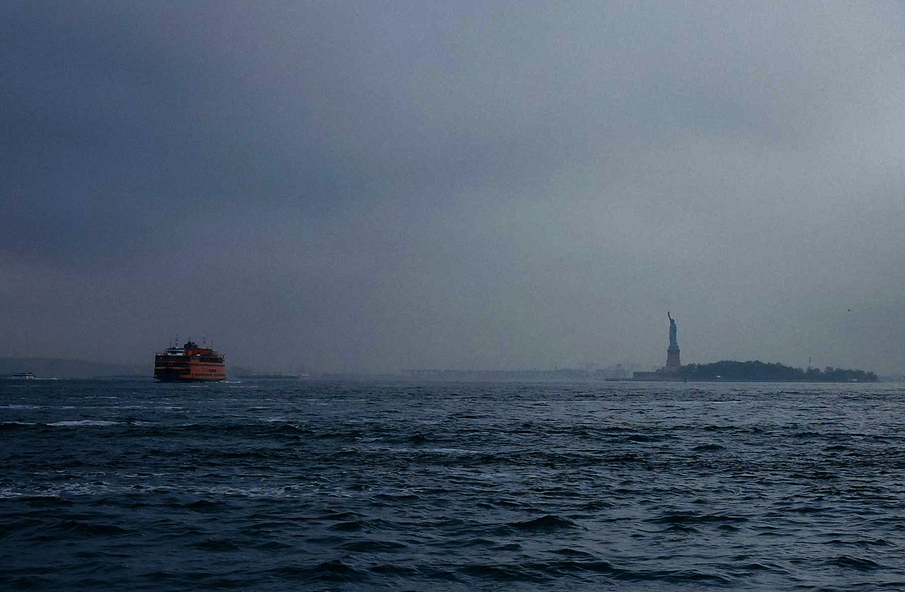 A dark sea with the statue of liberty on the right and a ferry on the left.