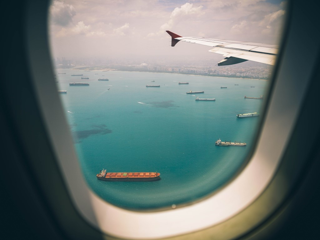 Photo taken looking out of a plane's window down onto water with many ships