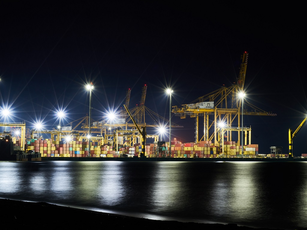 A port at night with many lights on.